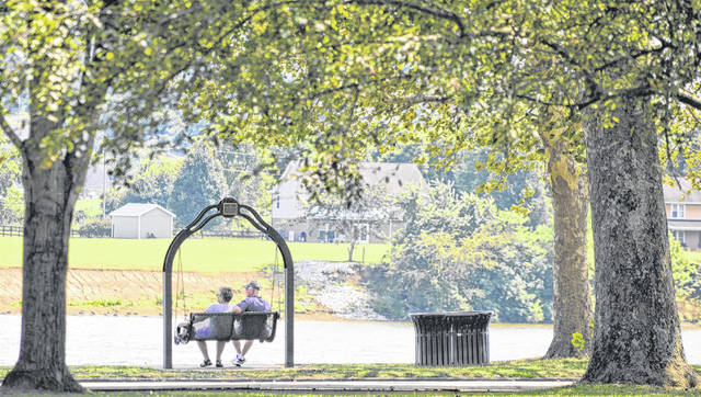 A couple sits in Gallipolis City Park on a warm afternoon, watching the Ohio River drift by. The oppressive heat of recent days is moving out of the area, making way for a weekend with temperatures expected to reach highs in the low 80's.