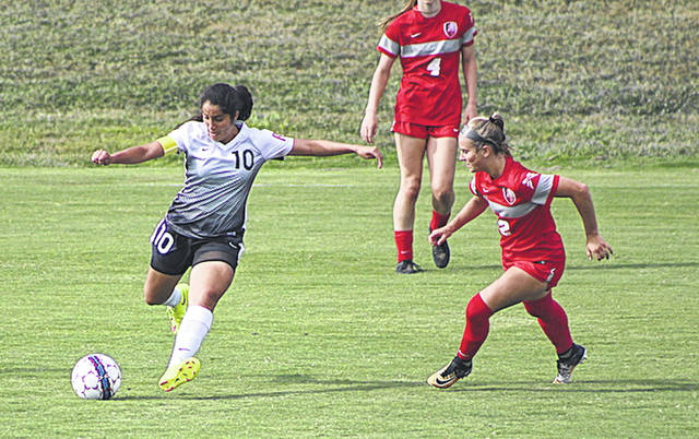 Rio Grande's Ambar Torres sets to send a pass toward a teammate during Saturday night's 5-0 loss to Indiana Wesleyan University at Evan E. Davis Field.