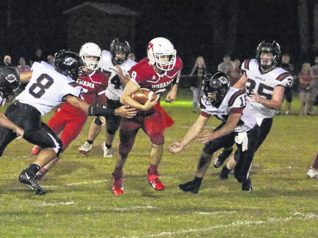 Wahama senior Abram Pauley, middle, runs between a handful of Ravenswood defenders during the first half of Friday night's season opening football contest at Bachtel Stadium in Mason, W.Va.