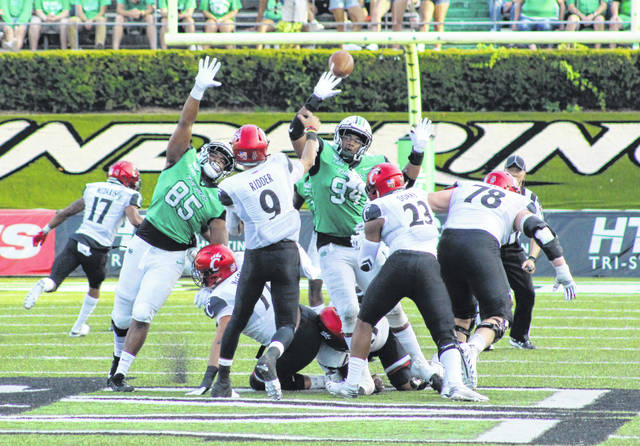 Marshall defenders Milan Lanier (85) and Channing Hames (94) apply pressure as Cincinnati quarterback Desmond Ridder (9) delivers a pass down field during the first half of Saturday's non-conference football game at Joan C. Edwards Stadium in Huntington, W.Va.