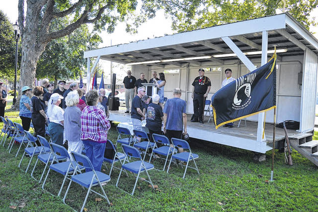 Visitors in Gallipolis City Park stand for the National Anthem during the annual National Prisoners of War and Missing in Action Recognition Day ceremony in September 2018.