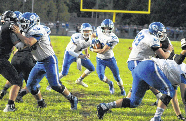 Gallia Academy junior Michael Beasy (20) takes a handoff from quarterback Noah Vanco and runs up the middle during the first half of Saturday night's Week 2 football contest against River Valley in Bidwell, Ohio.