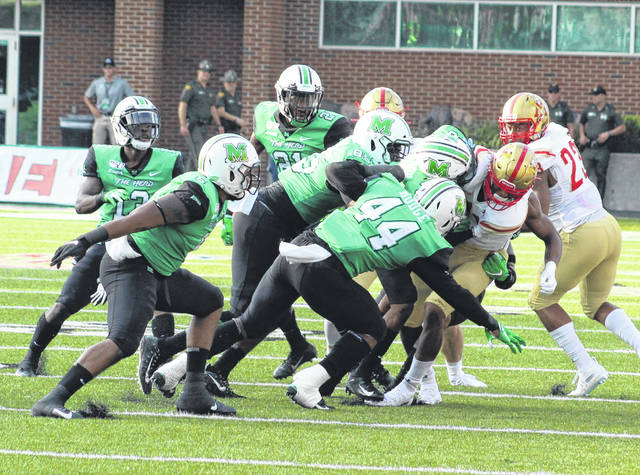 Marshall defenders Chris Jackson, Milan Lanier (85) and Darius Hodge (44) bring down a VMI receiver during the first half of Saturday's season-opening football contest at Joan C. Edwards Stadium in Huntington, W.Va.