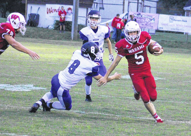 Wahama senior Trevor Hunt (5) breaks away from a Miller defender during a first quarter run Friday night in a Week 2 TVC Hocking football contest at Bachtel Stadium in Mason, W.Va.