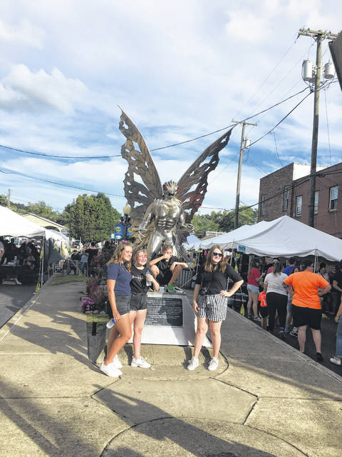 Several festival goers are seen taking their picture with the Mothman statue throughout the Mothman Festival.