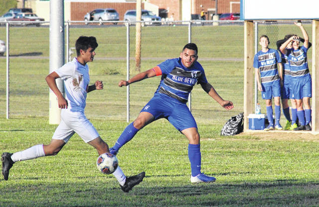 Gallia Academy senior Emmanuel Valadez (17) passes the ball around a West defender, during the Blue Devils' 9-1 sectional quarterfinal victory on Monday in Centenary, Ohio.
