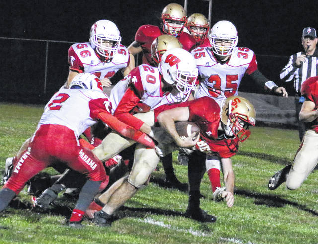 South Gallia senior Kyle Northup is dragged down by Wahama defenders Kase Stewart (2) and Gavin Stiltner (20) during the second half of Friday night's TVC Hocking football contest in Mercerville, Ohio.