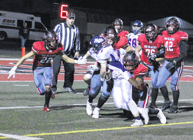 Point Pleasant defenders Nick Leport (22), Mark Fowler and Jovone Johnson wrestle down Man running back Cameran Frye during the first half of Friday night's Week 9 football contest at OVB Field in Point Pleasant, W.Va.