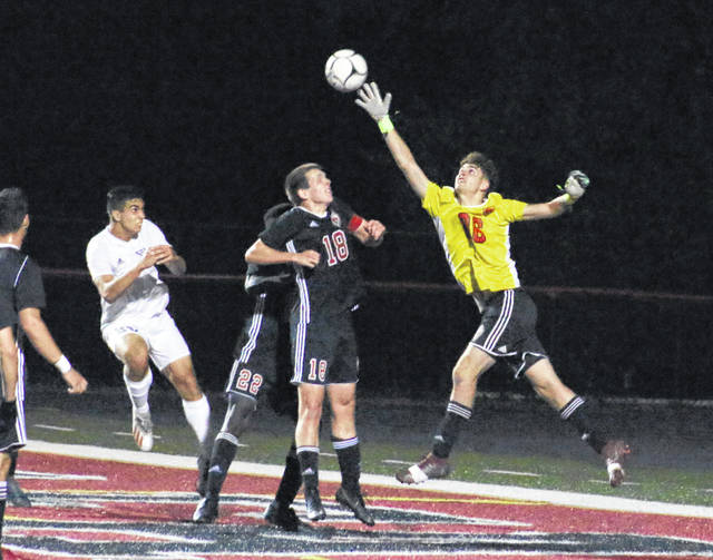 Point Pleasant keeper Nick Smith leaps to deflect a ball away from the goal during the first half of Tuesday night's Region IV championship match against Winfield at OVB Field in Point Pleasant, W.Va.