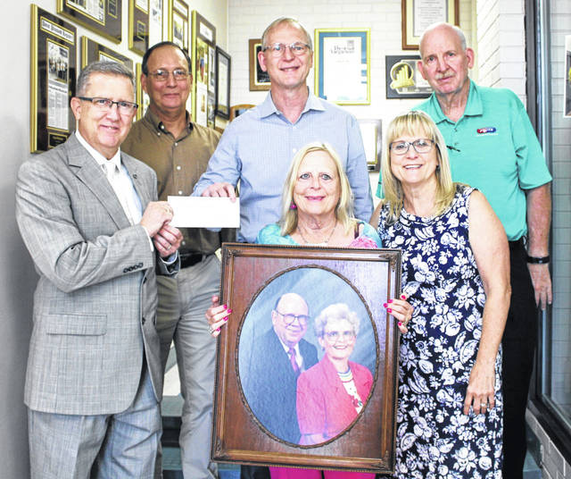 "Pictured back row, from left, Rev. S. Jeff Anderson, Jim Rossi, John Fruth, Mike Fruth; from row, from left, Joan Fruth, Lynne Fruth. Joan is holding a portrait of her parents, Jack and Frances ""Babs"" Fruth."