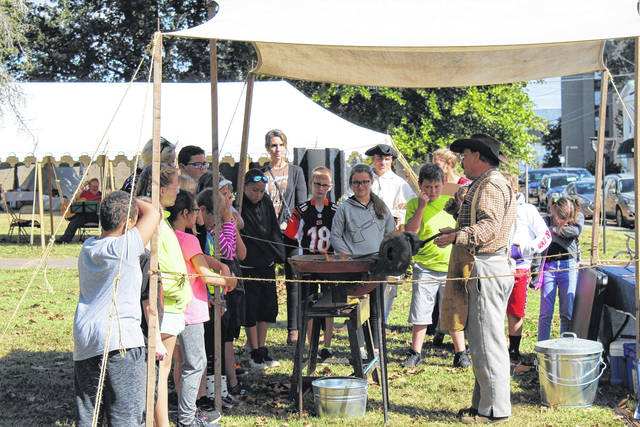 Students hear from the festival's blacksmith.