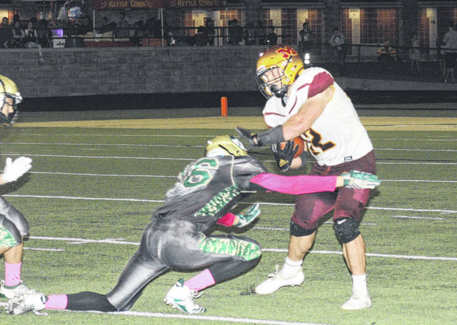 Meigs junior Abe Lundy, right, tries to elude an Athens defender during Friday night's TVC Ohio football contest in The Plains, Ohio.