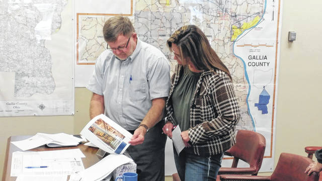 Gallia Commissioner Brent Saunders shows area resident Sherry Russell examples of potential model plans for a new Gallia Jail.