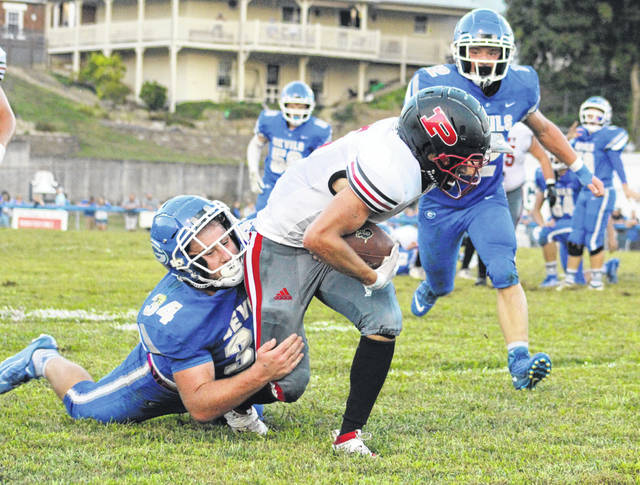 Gallia Academy senior Cade Roberts (34) brings down Point Pleasant receiver Zane Wamsley during a Sept. 13 contest at Memorial Field in Gallipolis, Ohio.