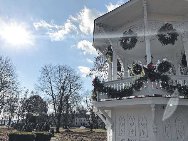 "The weather cleared up on Sunday, allowing some of those particpating in the annual Gallipolis in Lights ""Tree Walk"" to complete their decorating duties. Pictured is the historic Bandstand in City Park, adorned with greenery and wreaths."
