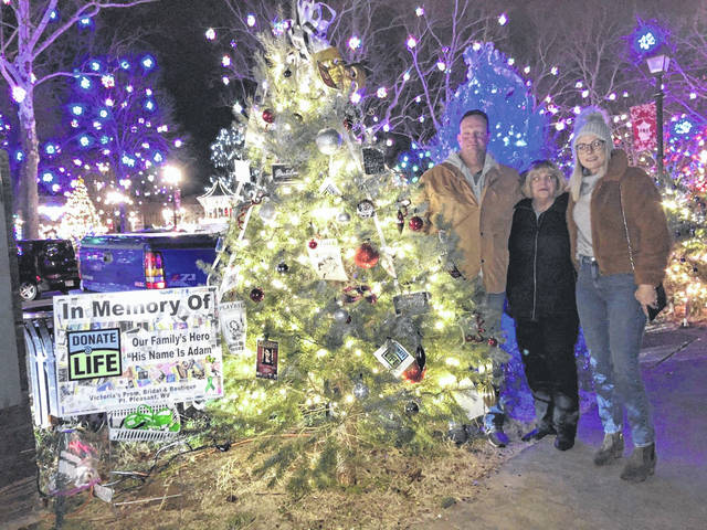From left to right, Robert Edwards, Monica Edwards and Kara Haan stand next to a tree dedicated to organ donor, Adam Carter.