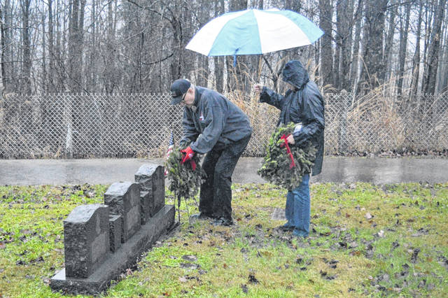 Visitors leave wreathes on the graves of deceased veterans in Tyn Rhos Cemetery.