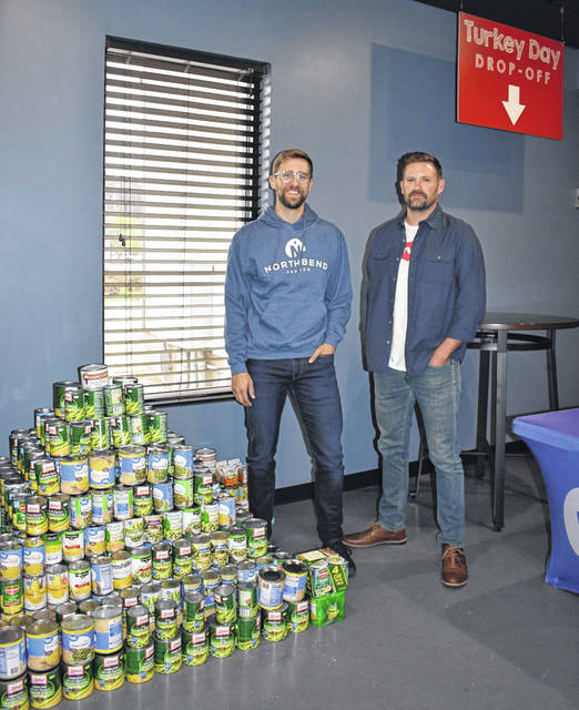 Northbend Church Pastor Jason Simpkins, right, and Jake Marburger, church creative director, are shown next to some of the canned items brought in for the church's inaugural Turkey Day Giveaway. Complete Thanksgiving meals will be distributed to 100 local families on Nov. 16, beginning at 9 a.m., on the Pomeroy parking lot. The food will be given on a first come, first serve basis, with no requirements.