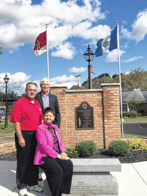 Pictured with the new flags recently added to the Gold Star Mothers Memorial are Colonel Charles Lewis Chapter DAR Flag Chairman Diana Cromley seated along with President of the Point Pleasant Chapter of the SAR/Memorial Committee member Ed Cromley and President of the Mason County Commission Rick Handley.
