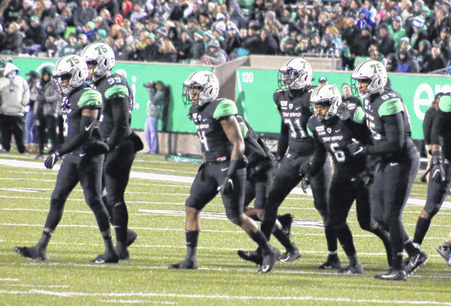 "Pictured are members of the defensive team for the Thundering Herd on Friday, wearing black uniforms and ""75"" on their helmets. A green stripe at the center of the helmet contained the names of the victims of the fatal plane crash."