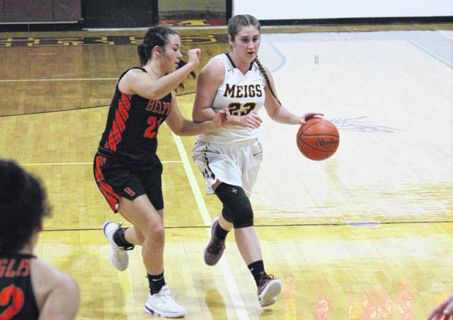 Meigs junior Jerrica Smith (23) drives past Belpre's Kaitlin Bush, during the Lady Marauders' non-league setback on Monday in Rocksprings, Ohio.