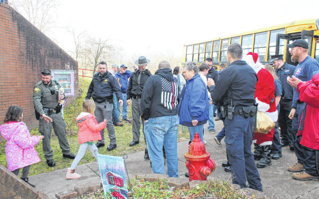 First responders and friends high-five kids as they board the bus to go shop on Monday morning.