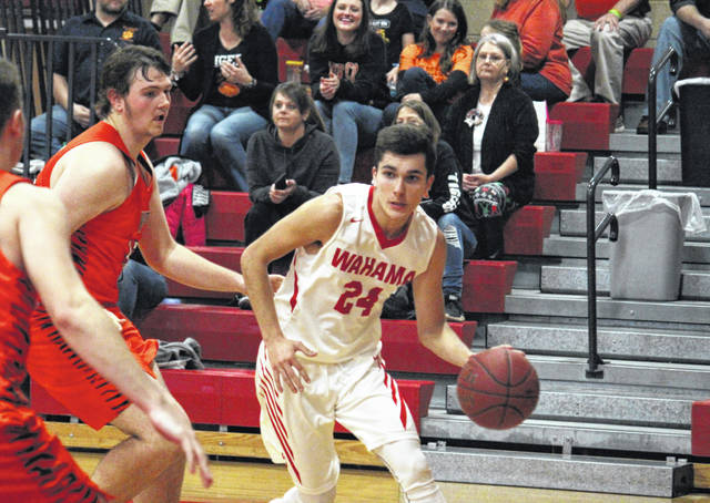 Wahama senior Hunter Board (24) drives past a pair of Tiger defenders, during Wirt County's 64-46 victory on Monday at Gary Clark Court in Mason, W.Va.