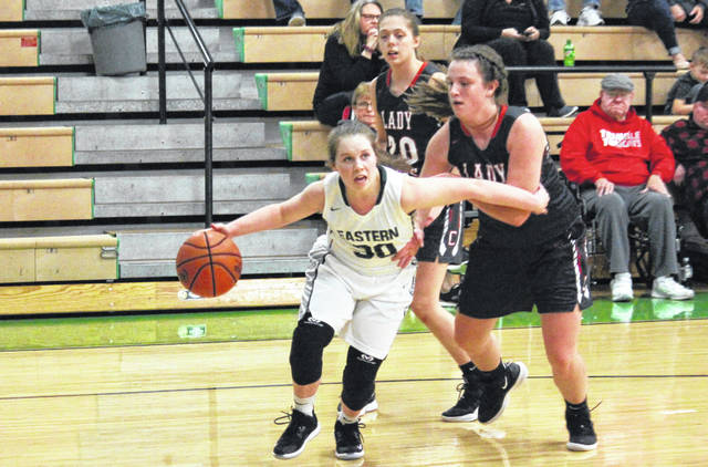 Eastern freshman Jennifer Parker (30) drives past a pair of Lady Tomcats, during the Lady Eagles' 57-45 setback on Monday in Tuppers Plains, Ohio.