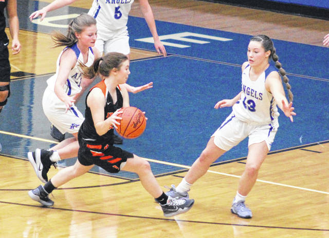 Gallia Academy defenders Regan Wilcoxon and Preslee Reed (13) apply pressure to an Ironton ball-handler during the second half of Monday night's OVC girls basketball contest in Centenary, Ohio.