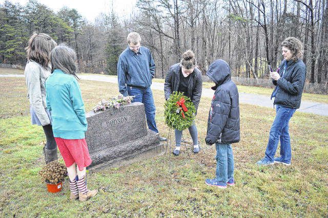 Family members Ilo Dodson, Barley Dodson, Emma Dodson, Lori Taylor and Morgan Taylor set a wreath near the grave of loved one, Dale Dodson.