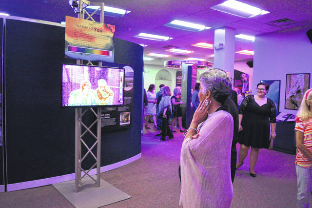 Visitors explore SPACE: A Journey to Our Future during the exhibit's opening at the Bossard Memorial Library in September. One visitor inspects the curiosity of thermal imaging technology.