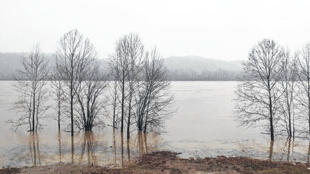Snow falls Tuesday over a flooded Ohio River after heavy rains Monday in Gallia County. The Gallia Emergency Management Agency reported as of 3 p.m., Tuesday, high water at Reese Hollow off of Addison Pike, Ohio 554 at Stingy Creek Road, Vanzant Road, Spruce Street Extension, Ohio 554 and White Oak Road, Patriot Road at Burnette Road, Ingalls Road near Bakers Landing, Scenic Road, Ohio 325 south of Vinton, Ohio 233 between Ohio 141 and the Jackson County line, Ohio 141 at Cadmus, Ohio 325 north of Ohio 160, Bulaville Pike off Ohio 554 by the bridge, Roush Hollow Rod off Addison Pike, Brick School Road, Ohio 75 between Ohio 141 and county line, Alice Rod, Andrews Road, Strong Run Road, McMillin Road, Ohio 554 at Raccoon Creek with one-lane covered. The Gallia Emergency Management Agency asks the public to contact them if they find any other high water areas at 740-441-2036.