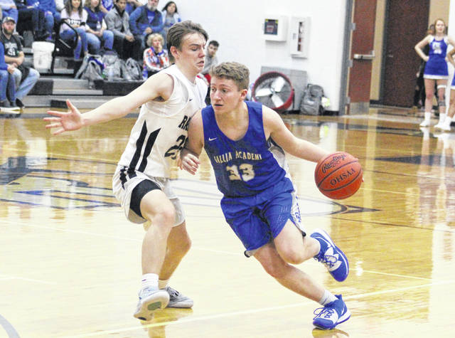 Gallia Academy senior Justin Wilcoxon (33) dribbles around River Valley defender Mason Rhodes during the second half of Saturday night's boys basketball contest in Bidwell, Ohio.