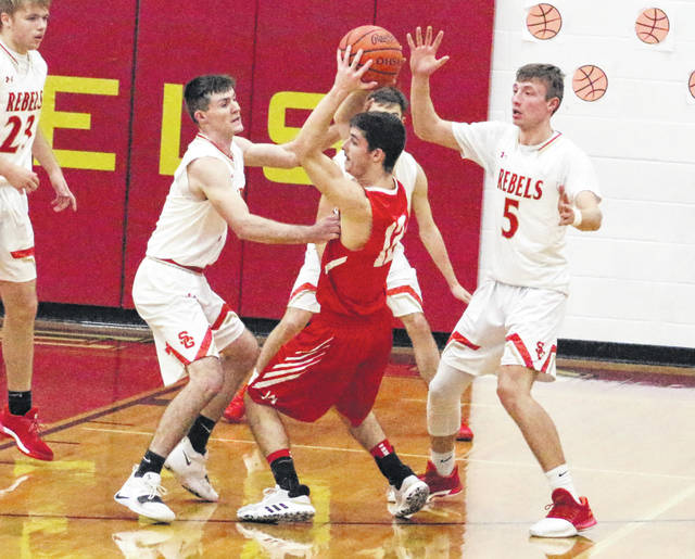 South Gallia defenders Kyle Northup, left, and Jared Burdette (5) apply pressure to Wahama's Abram Pauley during the first half of Tuesday night's boys basketball game in Mercerville, Ohio.
