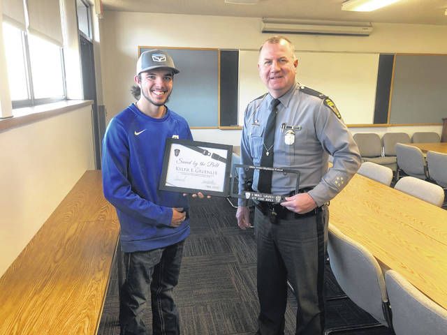 Kyler Greenlee stands with Ohio State Highway Patrol Gallipolis Post Commander Lt. Barry Call with his Saved by the Belt Club recognition.