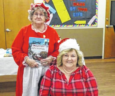Pictured is Vickie Powell, standing and dressed as Mrs. Claus. Elf Gail Belville (seated) assists her as she reads Mountain Christmas to the group.