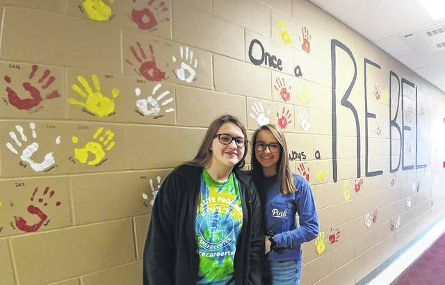South Gallia Junior Makayla Waugh and Sophomore Jaleigh White stand with the Once a Rebel wall as organizers of the art effort. Not pictured: fellow organizers Sophomore Shawna Waugh and Freshman Lily Martin, both were reported as absent due to sickness.