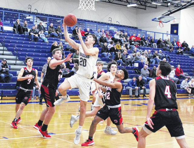 River Valley junior Jordan Lambert (20) releases a shot attempt between a pair of Circleville defenders during the second half of Monday night's Division II boys basketball sectional quarterfinal basketball game at Southeastern High School in Londonderry, Ohio.