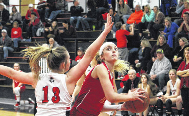 Wahama junior Emma Gibbs goes up for a low-post shot over RHS sophomore Lindsay Carroll (13), during the Lady Falcons' 62-32 victory on Monday in Ravenswood, W.Va.