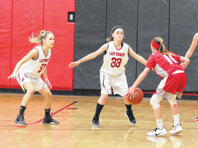 Point Pleasant senior Lena Zellinger, left, and freshman Patience Burke (33) apply pressure to a Poca player during the first half of Thursday night's girls basketball game in Point Pleasant, W.Va.