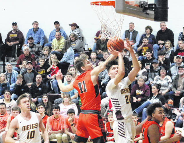 Meigs senior Weston Baer (20) releases a shot attempt over a Nelsonville-York defender during a Feb. 16 boys basketball contest at Larry R. Morrison Gymnasium in Rocksprings, Ohio.