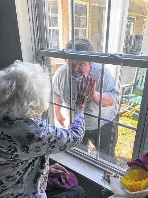 Bobbie Holzer, a resident of Holzer Assisted Living, receives a socially distant (and safe) greeting from her grandson, Alex Irvin. This photo taken by Carla Crawford, activity coordinator for Holzer Assisted Living.