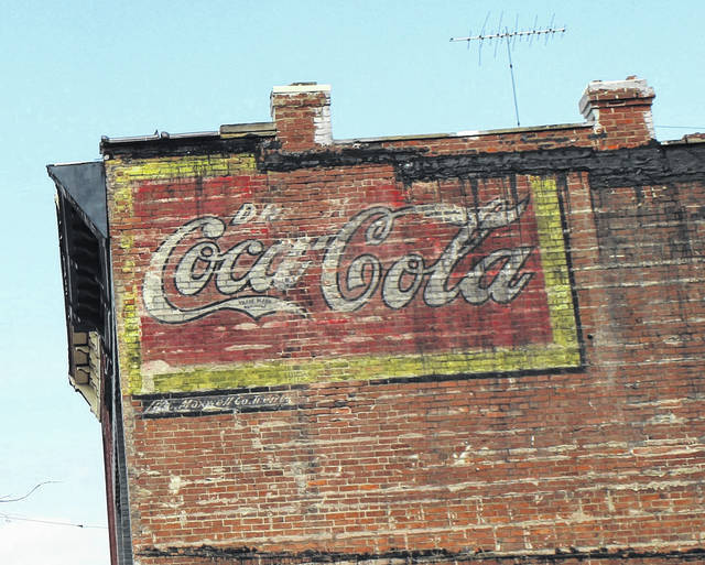 """While preparing the new site for the Point Pleasant River Museum and Learning Center, recently, when the common wall between the old Harris' Steak House and the former Double D lounge was removed, a relic from another time appeared. According to the Mason County Historical and Preservation Society, based on Coca-Cola's own company history, this advertisement was put up sometime between 1890 and 1940, which can be determined by the """"Trade Mark Registered"""" tucked into the tail of the first """"C."""" Chris Rizer of the Society said, """"We can narrow that down a bit further using what we know about the buildings; 324 Main (Harris') was built ca. 1895, and 320 Main (the Double D) was built ca. 1935."""" (Beth Sergent 