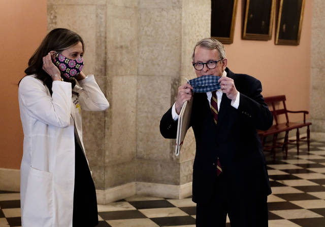 Dr. Amy Acton, left, director of the Ohio Department of Health, and Ohio Gov. Mike DeWine pose with their homemade masks following a news conference on the state of Ohio's response to the ongoing COVID-19 pandemic on Monday, April 6, 2020, at the Ohio Statehouse in Columbus, Ohio. (Joshua A. Bickel/The Columbus Dispatch via AP)
