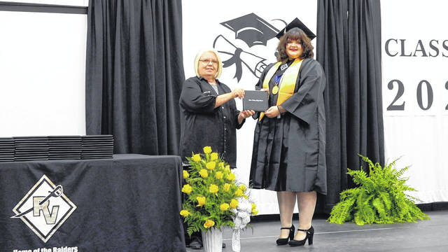 President of the Gallia County Local Schools Board of Education, Beth James, presents graduate Katie Leann Baker with her diploma from River Valley High School. (Mike Thompson | Courtesy)