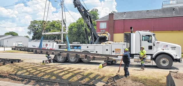Employees from Reds Rollen Garage help place track at the Gallipolis Railroad Freight Station Museum. (Gallia County Chamber of Commerce | Courtesy)