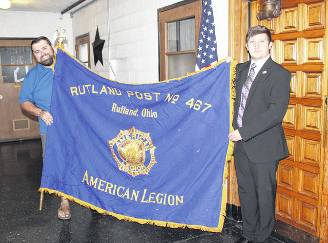 Historian Jordan Pickens and Rutland Mayor Tyler Eblin are pictured with the Rutland American Legion Post 467 flag which Pickens donated to the village.