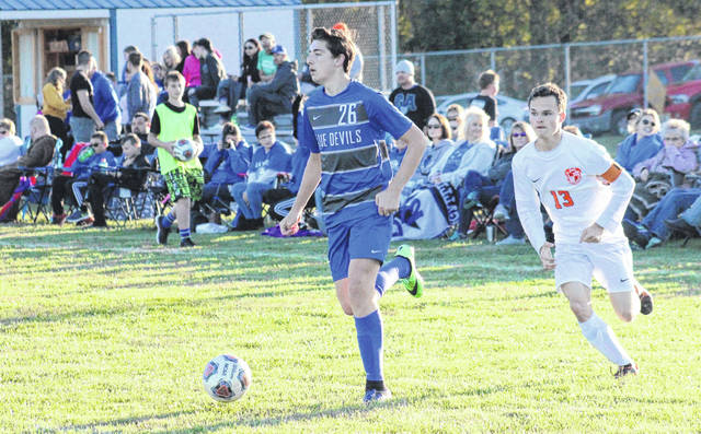 Gallia Academy's Brody Wilt (26) drives past a Portsmouth West defender, and spectators, during an Oct. 14, 2019 match at Lester Field in Centenary.
