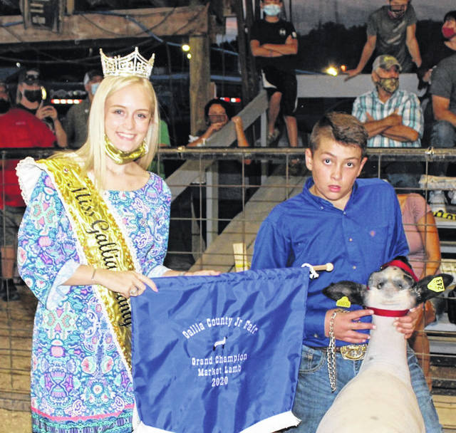 Rees Toler works the show ring and takes home Grand Champion Market Lamb. Toler is pictured with Miss Gallia County Abby VanSickle. (Dale Lear | Photo)