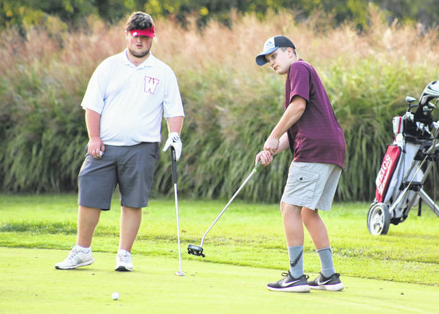 Meigs sophomore Gunnar Peavley, right, hits a putt attempt on the ninth hole during a Sept. 22 golf match at Riverside Golf Course in Mason, W.Va.